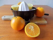 Squeezer with fresh oranges and lemons sliced on wooden board. Squeezer with fresh vitamin c oranges and lemons for winter health on wooden board Royalty Free Stock Images
