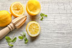 Squeezer and lemons. On wooden table Royalty Free Stock Photos