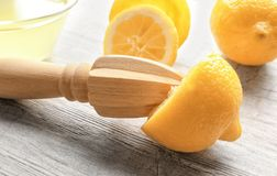 Squeezer and lemons. On wooden table Stock Photos