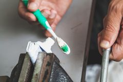 Squeezes toothpaste from tube with vise. Very thrifty person squeezes the toothpaste from the tube onto a twisted brush clamped in the bench stock image