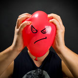 Squeezing angry balloon Stock Photography