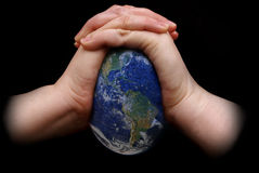 Squeezing the Earth. A pair of hands squeezing the Earth with cracks appearing all over the surface and the oceans. Blue Marble picture courtesy of NASA, see for Royalty Free Stock Photo