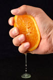 Squeezing a half orange. On a black background Royalty Free Stock Images