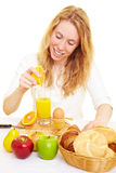 Squeezing juice. Woman at the breakfast table squeezing fresh orange juice royalty free stock image