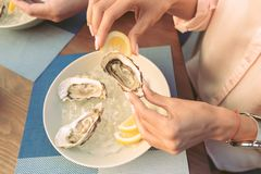 Accurate woman carrying opened oyster and adding lemon juice. Squeezing lemon juice. Accurate women carrying opened oyster and adding lemon juice for the high stock photography