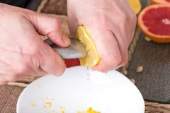 Squeezing lemon with metal spoon. Stock Images