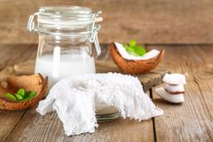Squeezing milk from the chips of coconut in the gauze on an old. Wooden table Stock Image
