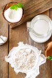 Squeezing milk from the chips of coconut in the gauze on an old wooden table. Squeezing milk from the chips of coconut in the gauze on an old wooden table Royalty Free Stock Photo