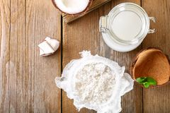 Squeezing milk from the chips of coconut in the gauze on an old wooden table. Squeezing milk from the chips of coconut in the gauze on an old wooden table Royalty Free Stock Image