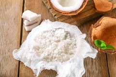 Squeezing milk from the chips of coconut in the gauze on an old wooden table. Squeezing milk from the chips of coconut in the gauze on an old wooden table Stock Photography