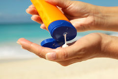 Squeezing sun protection cream. Women on the beach squeezing sun protection cream Stock Images