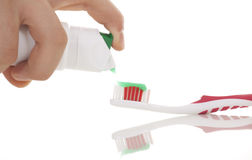 Squeezing toothpaste onto toothbrush Royalty Free Stock Photo