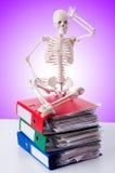 Squelette avec la pile des dossiers contre le gradient Photo stock