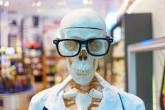 Squelette factice d'os dans une robe médicale blanche photos stock