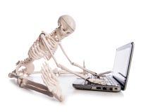 Squelette travaillant sur l'ordinateur portable Photos libres de droits