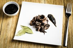 Squid cooked in a white plate with a fork, a bowl of ink and a few bay leaves. Squid cooked on a white plate next to a fork, a bowl with ink and some bay leaves royalty free stock photos