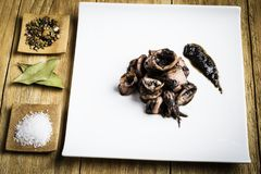 Squid cooked on a white plate next to some spices, salt and some bay leaves. Squid cooked on a white plate next to some spices, salt and bay leaves on a wooden stock photos