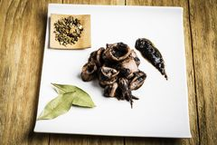 Squid cooked on a white plate next to some spices and some bay leaves. On a wooden board stock image