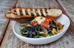 Squid ink fettuccine and bread. A plate of squid ink fettuccine with seafood and toasted breads Royalty Free Stock Image