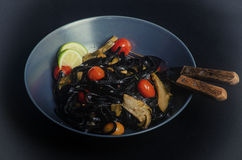 Squid ink pasta. With artichoke and tomatoes royalty free stock photos
