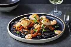 Squid ink pasta with prawns and scallops. In rich tomato sauce on black plate stock photo