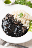 Squid in ink with rice and parsley. Squid in its own ink with brown rice and parsley sauce. Traditional Spanish recipe Royalty Free Stock Photography