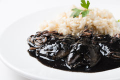 Squid in ink with rice and parsley. Squid in its own ink with brown rice. Traditional Spanish recipe Royalty Free Stock Photography
