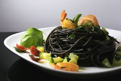 Squid ink spaghetti with shrimp and zucchini royalty free stock photos