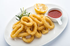 Squid rings in batter. Lemon, red sauce Royalty Free Stock Photo