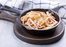 Squid rings fried with onions royalty free stock photos