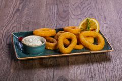 Squid rings with sauce. Served lemon royalty free stock photo