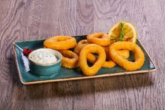 Squid rings with sauce. Served lemon royalty free stock images