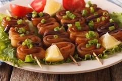 Squid rings on skewers with lemon macro. horizontal Royalty Free Stock Photo
