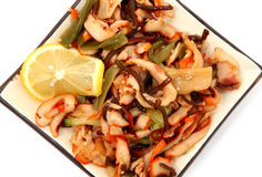 Squid Salad. With seaweed, sesame seed, onions and lemon slice Stock Photos