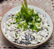 Squid salad with mushrooms and green peas. Squid salad with mushrooms and green pepper in a bowl on the holiday table Royalty Free Stock Image