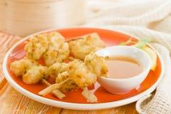 Squid Tempura Skewers. Battered and deep fried calamari on skewers. Served with mango dip Stock Photos