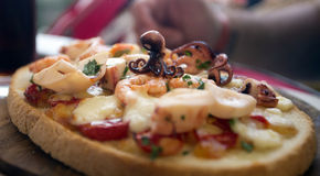 Squid topped seafood pizza or bruschetta Stock Image