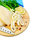 Squid with lemon and knife on a round board Stock Image