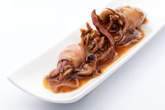 Squids in hot pepper sauce. Snack squids conserve in hot pepper sauce on a white background Stock Photos