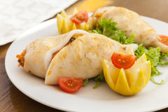 Squids stuffed with seafood on white plate Stock Images