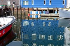 Squigly reflections in waterfront scene. The squigly reflections of a dock building and boats moored at the Portland, Maine, waterfront royalty free stock photo