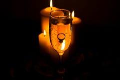 Squilli in un vetro del champagne e negli indicatori luminosi della candela immagini stock libere da diritti