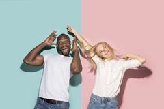 The squint eyed couple with weird expression on blue and pink studio. I lost my mind. The squint eyed couple with weird expression. Beautiful female half-length stock image