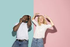 The squint eyed couple with weird expression on blue and pink studio. I lost my mind. The squint eyed couple with weird expression. Beautiful female half-length royalty free stock photo