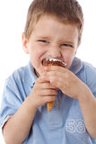 Squinting boy eating ice cream. Squinting boy eating the cone of ice cream, isolated on white Stock Photo