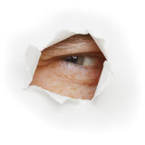 Squinting eye looks through a hole Royalty Free Stock Images