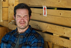 Squinting Male in front of crates Stock Photo