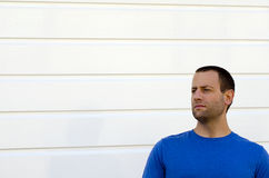 Squinting man. In a blue shirt and white background Stock Photo