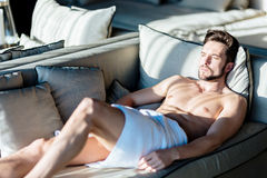 Squinting young, beautiful male relaxing on a couch in a hotel Stock Images