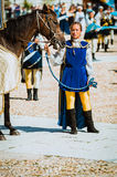 Squire Beautiful female with her horse in medieval parade stock images